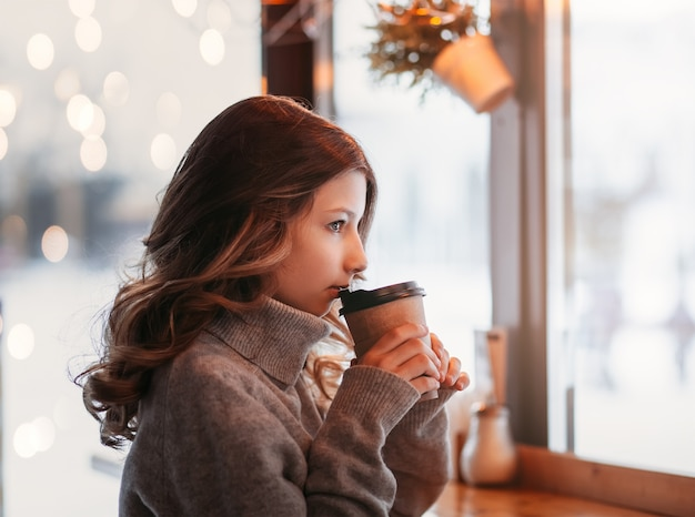 Young girl drinks coffee from a paper cup in a cafe by the window