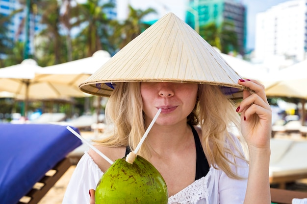 Молодая девушка пьет из кокоса в традиционной азиатской конической шляпе, сидя на пляже