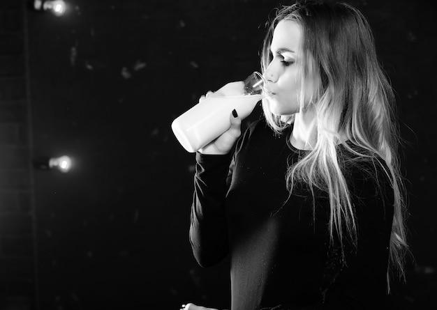어린 소녀는 검은 벽 배경에 있는 병에서 우유를 마신다