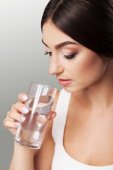 어린 소녀는 물을 마신다. 얼굴의 건강한 모습. 여자의 초상화입니다. 아름다움과 건강의 개념. 회색 배경.