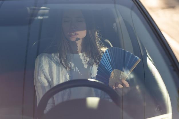 Молодая девушка-водитель страдает от жары в вентиляторе автомобиля с сломанной системой климат-контроля
