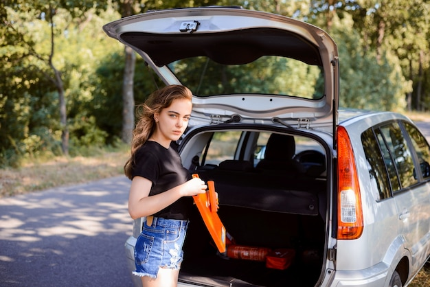 Young girl driver takes emergency sign from the car trunk