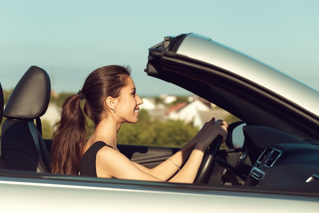 Young girl driving cabrio car