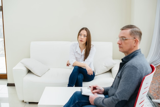 A young girl during depression communicates with a psychologist in the office. psychological help.