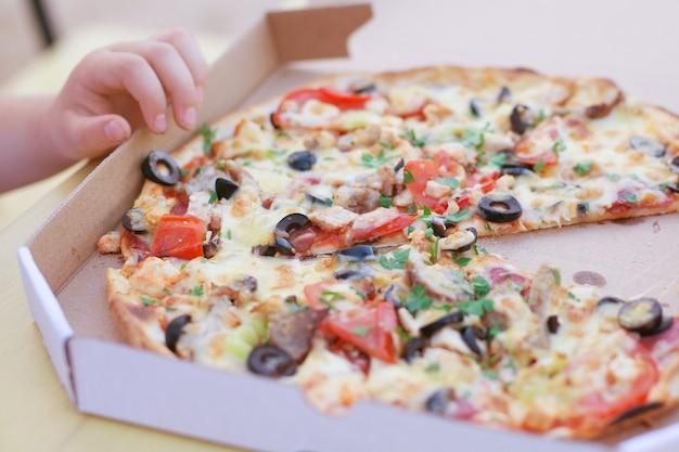 어린 소녀는 판지 상자에서 맛있는 이탈리아 피자를 먹는다