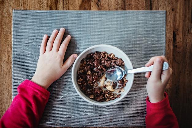 우유와 함께 아침 시리얼을 먹는 어린 소녀. 샷 바로 위, 손과 그릇의 클로즈업.