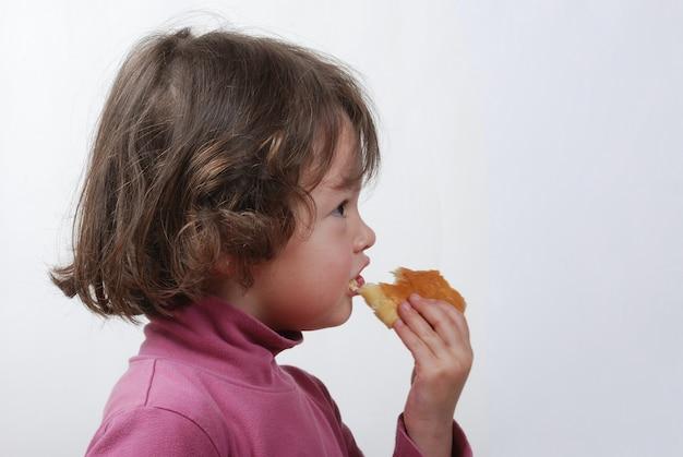 A  young girl eating a bun