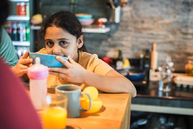 ダイニングテーブルでボウルに食べ物を食べる若い女の子