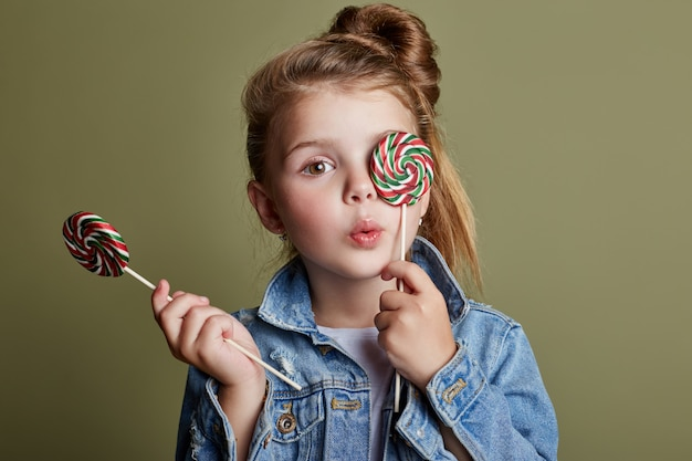 Young girl eating round candy licks lollipop