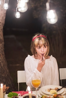 Young girl eating with fork at christmas dinner