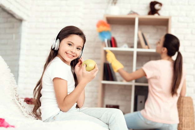 Young girl eats an apple and rests while her mother cleaning