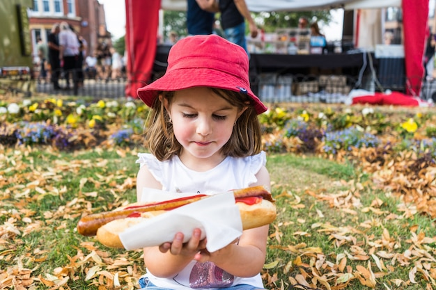 A young girl eats a hot dog.large german sausage in bun.