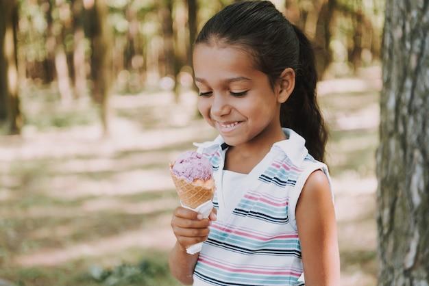 Young girl eats ice cream in wood.