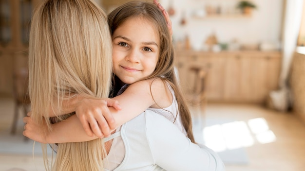 Young girl embracing her mother while at home