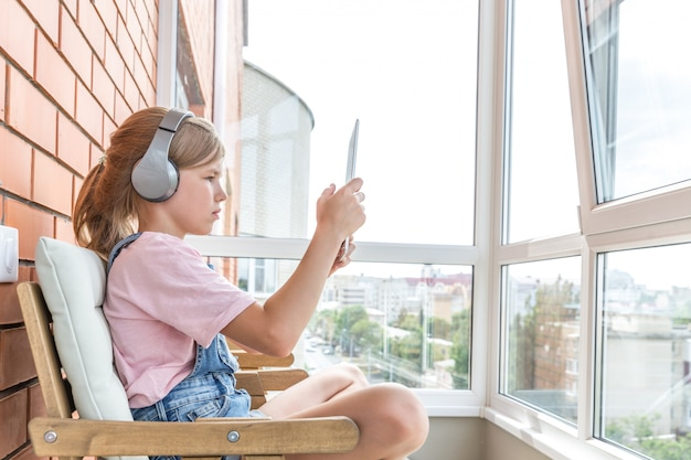 A young girl enjoying listening to music on her headphone with tablet