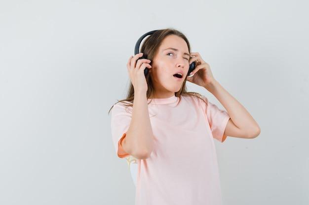 Ragazza che gode della musica con le cuffie in maglietta rosa e guardando pensieroso. vista frontale.