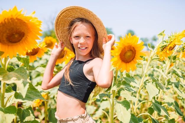 Молодая девушка, наслаждаясь природой на поле подсолнухов.