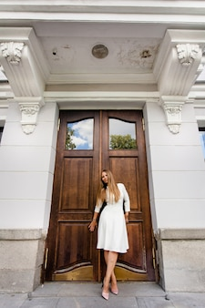 Young girl of european appearance in a white dress on the background of the building.