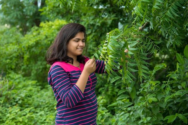 어린 소녀 검사 또는 필드에서 neem 나무 잎을 관찰
