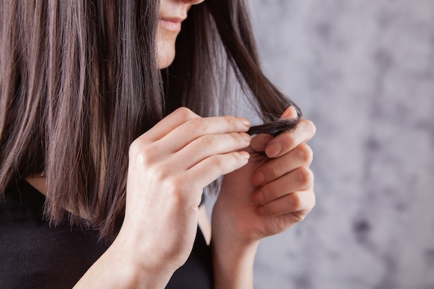 Young girl examines her hair. hair problem concept on gray