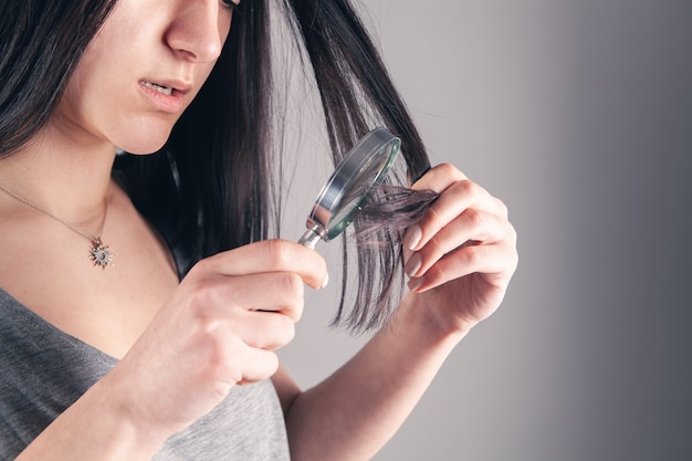 Young girl examines her hair with a magnifying glass. hair problem concept on gray
