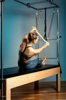 Young girl exercises on a bed of pilates reformers, in the hall on a background of a gray wall