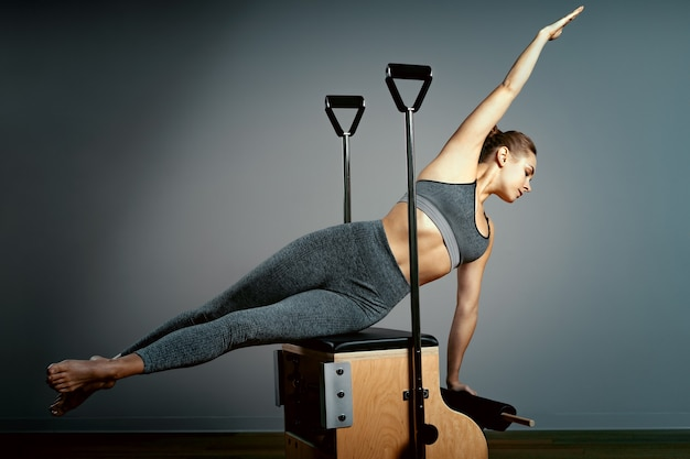 Молодая девушка делает упражнения на кровати реформаторов пилатеса