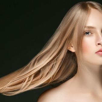 어두운 배경 위에 손으로 긴 금발 머리를 가진 어린 소녀 얼굴 아름다움 피부 초상화. 스튜디오 촬영.