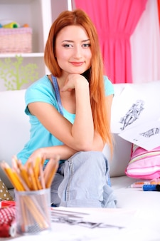 若い女の子のファッションデザイナーが服のコレクションを作成します