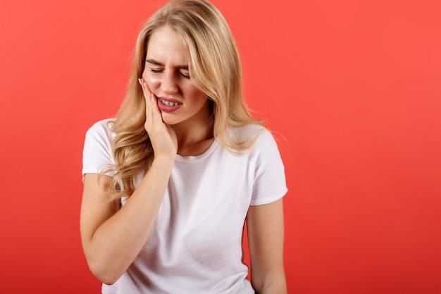 Молодая девушка чувствует боль, держа его за щеку одной рукой, страдает от сильной зубной боли