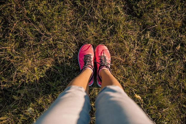 Young girl feet legs in sneakers on green meadow