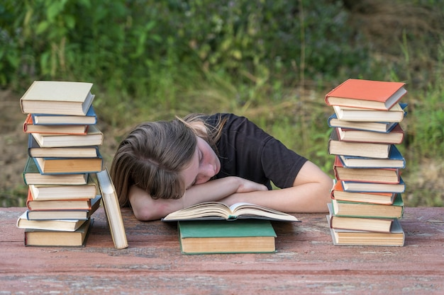 Young girl fell asleep after reading books on a wooden table in the garden