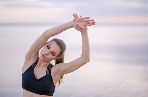 Young girl in fitness clothes by the sea performs exercises