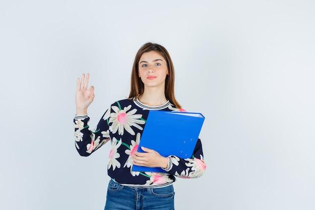 Ragazza in camicetta floreale, jeans che tengono cartella, mostrando gesto ok e guardando fiducioso, vista frontale.