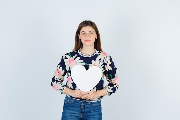 Giovane ragazza in camicetta floreale, jeans che tengono poster di carta e sembrano soddisfatte, vista frontale.