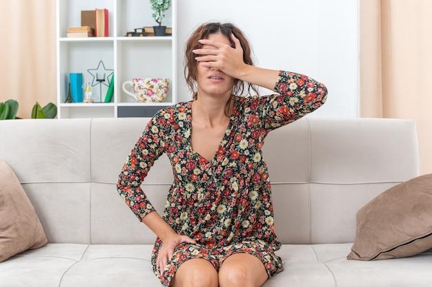 Giovane ragazza in abito floreale che copre gli occhi con la mano stanca e annoiata seduta su un divano in un soggiorno luminoso