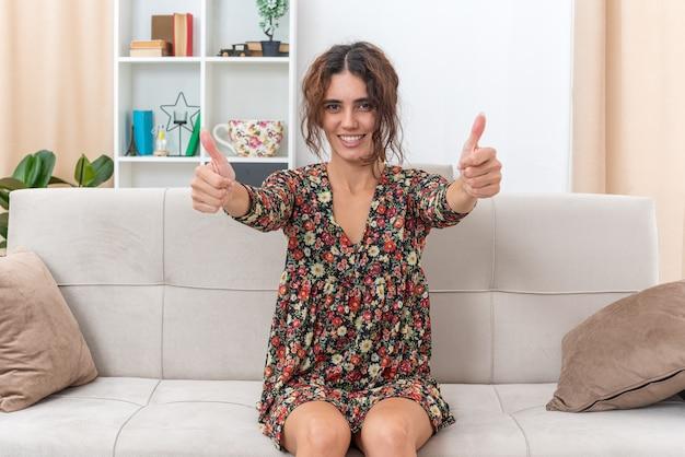 Giovane ragazza in abito floreale felice e positiva sorridente che mostra ampiamente i pollici in su seduta su un divano in un soggiorno luminoso