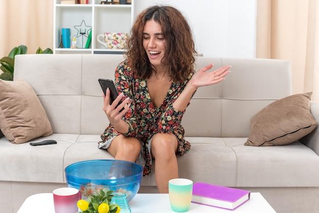 Giovane ragazza in abito floreale che tiene in mano uno smartphone guardando lo schermo felice ed eccitata seduta su un divano in un soggiorno luminoso