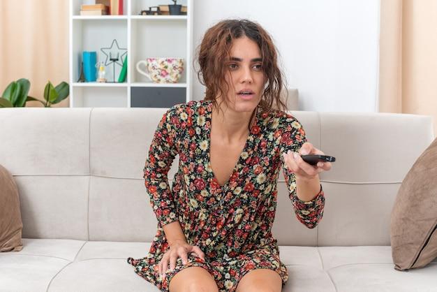 Giovane ragazza in abito floreale che tiene il telecomando della tv guardando la tv con una faccia seria seduta su un divano in un soggiorno luminoso light