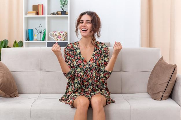 Giovane ragazza in abito floreale che sembra felice ed eccitata che stringe i pugni seduta su un divano in un soggiorno luminoso