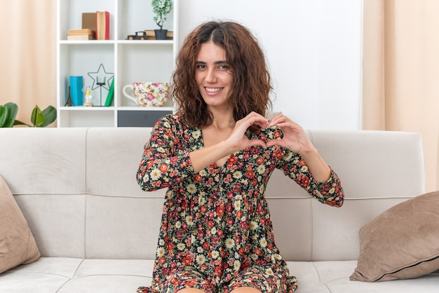 Giovane ragazza in abito floreale che sembra sorridente allegramente facendo il gesto del cuore con le dita seduta su un divano in un soggiorno luminoso