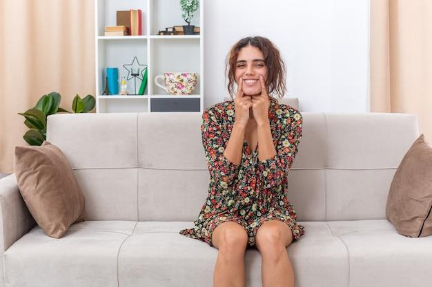 Giovane ragazza in abito floreale che punta con l'indice il suo sorriso seduta su un divano in un soggiorno luminoso