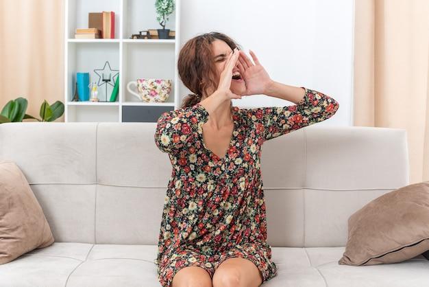 Giovane ragazza in abito floreale che grida o chiama qualcuno con le mani vicino alla bocca seduta su un divano in un soggiorno luminoso