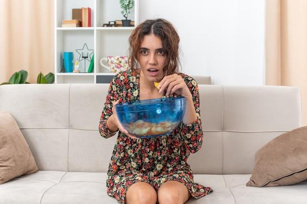 Giovane ragazza in abito floreale con una ciotola di patatine che mangia guardando la tv stupita e sorpresa seduta su un divano in un soggiorno luminoso