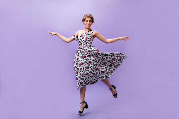 Young girl in fluffy dress jumps on purple background. lovely beautiful woman in colorful trendy clothes smiling on isolated backdrop.