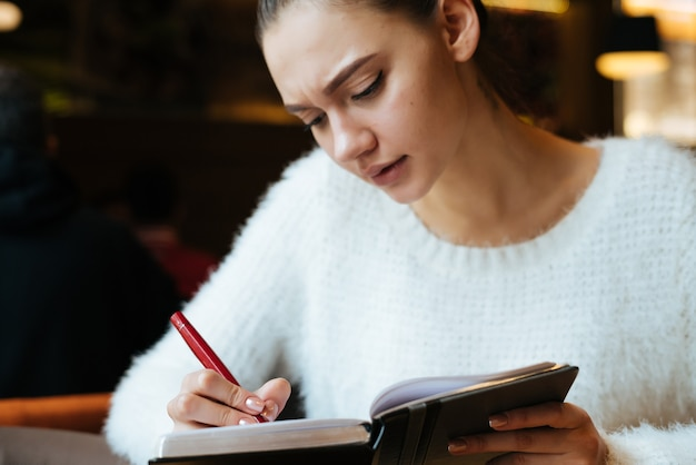 Young girl freelancer sits in a cafe, writes in a notebook, concentrates