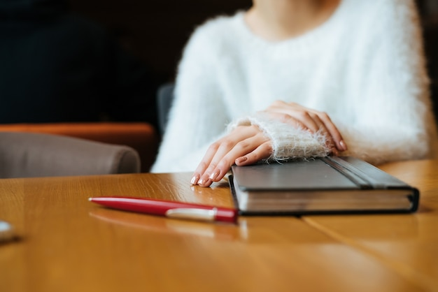 Young girl freelancer in a white sweater sits at a table in a cafe, on the desk lies a notebook