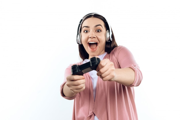 Young girl gamer in headphones with joystick