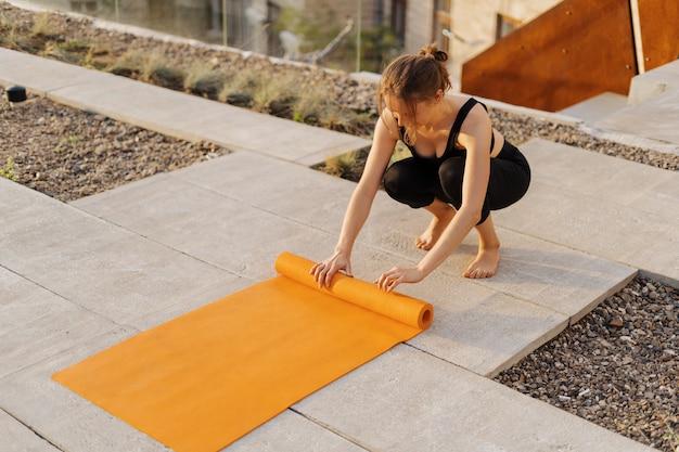 Молодая девушка готовится к занятиям спортом на открытом воздухе