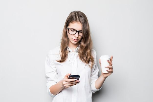 Giovane ragazza con gli occhiali vestita in t-shirt bianca da ufficio rigoroso si trova di fronte al muro bianco e tiene il suo telefono e la tazza di caffè nelle mani